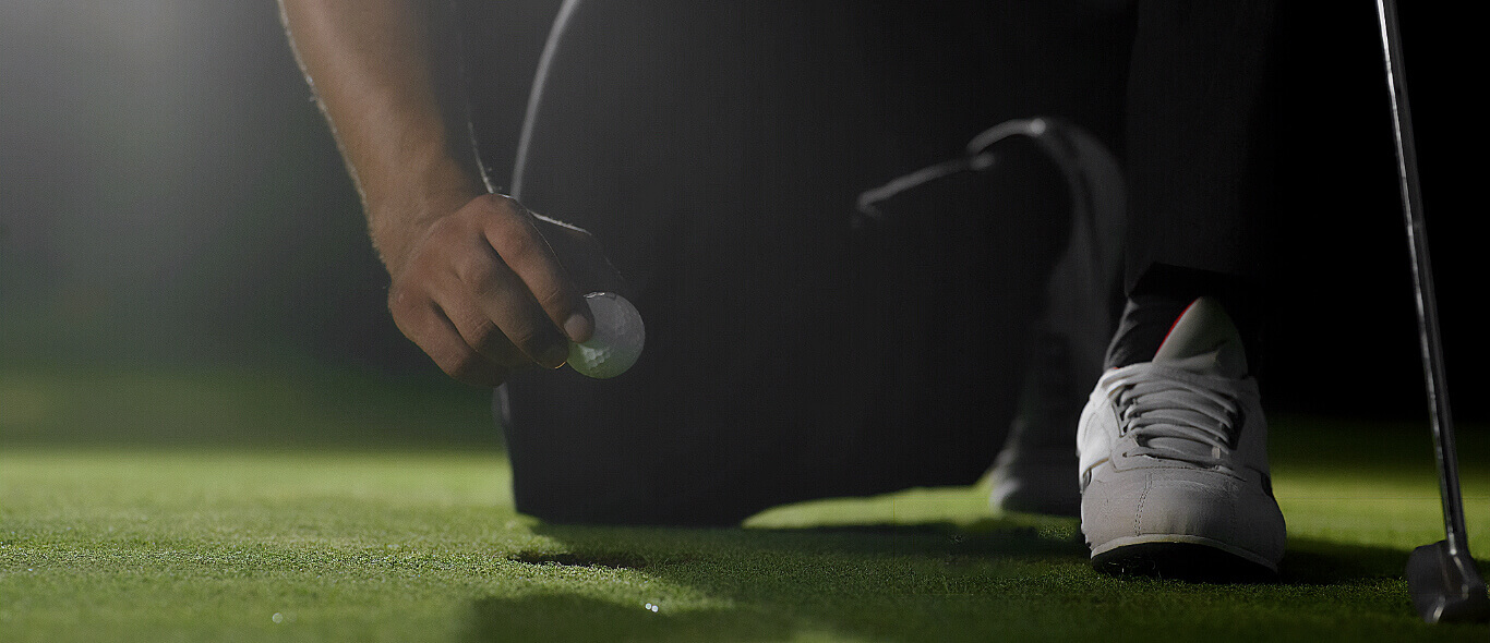Golfer kneeling, pulling golf ball out of hole